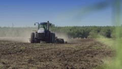 Rack Focus from Grass to a Tractor Discing a Field Stock Footage