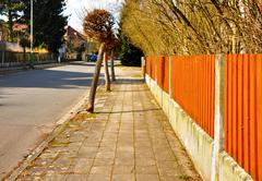 pedestrian path beside orange fence in town - stock photo