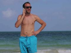 Man talking on cellphone in the beach, steadycam shot Stock Footage