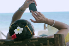 Woman typing on cellphone and lying on sunbed, closeup Stock Footage