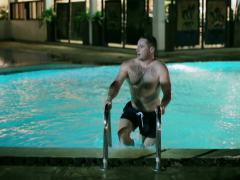 Man going out from swimming pool at night Stock Footage