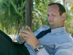 Businessman peeling orange on sunbed, steadycam shot Stock Footage