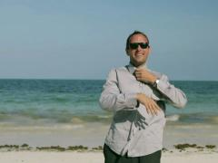 Happy businessman taking off his clothes on the beach Stock Footage
