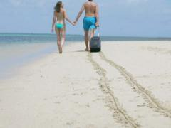 Couple walking on the beach and pulling luggage, steadycam shot Stock Footage