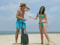 Lost couple argue on the beach and checking map - stock footage