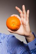 Diet and healthy nutrition. orange in male hand. Stock Photos