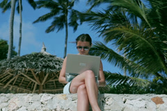 Woman working on laptop in exotic place Stock Footage