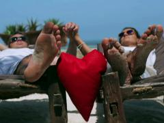 Red heart hanging betweem couple, steadycam shot Stock Footage