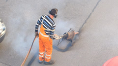 Slow Motion Construction worker heat up old Asphalte for applying new on road Stock Footage