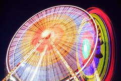 Amusement park at dusk - Ferris wheel in motion - stock photo