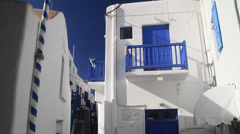 Mykonos resident leaves his white home with blue doors and shutters Stock Footage