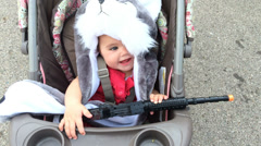 Cute kid with toy gun in stroller Stock Footage