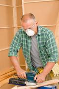 Handyman sanding wooden board diy home renovation - stock photo