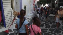Woman sweeps cobblestone street in front of shops in Mykonos Stock Footage