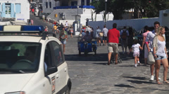 Delivery Motorcycle drives down a cobblestone street in Mykonos Stock Footage