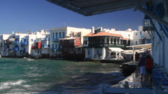 Waves crash into walkway of shops and restaurants in Mykonos Stock Footage