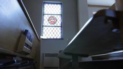 Dolly shot along church pews with stained glass window - stock footage
