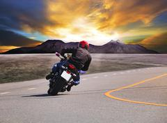 rear view of young man riding motorcycle in asphalt road curve with rural and - stock photo