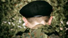Back of the head of a soldier in front of camouflage net Stock Footage