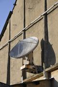 Very old dish antenna on a wall Stock Photos
