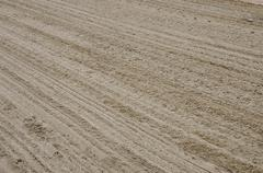 Sand texture with diagonal traces - stock photo