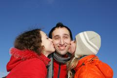 Two girl kissing guy - stock photo