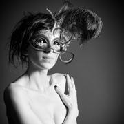 attractive nude woman wearing a mysterious venetian mask - stock photo