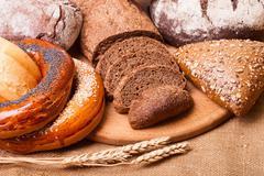 Fresh bread and wheat on the burlap Stock Photos