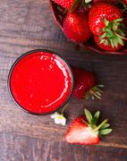 strawberry smoothie in glass jar, over old wood table - stock photo