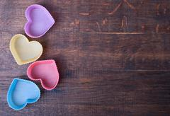 heart shaped silicon bun cases on wooden background - stock photo