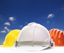 three of safety helmet construction protection on white against beautiful blu - stock photo