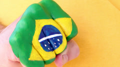 Brazilian football soccer fan doing winning gesture, brazilian flag on his fist Stock Footage