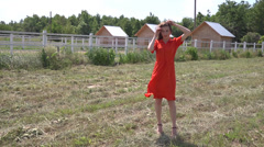Beautiful girl in countryside in a red dress - stock footage