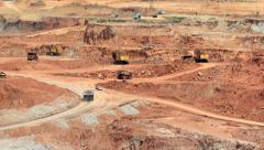 Mining dump trucks and excavators in the open pit mine Stock Footage