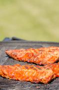spareribs on grill with hot marinade - stock photo