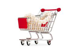Shopping cart and giftboxes on white - stock photo