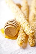 Grissini with sesame seeds and honey dipper Stock Photos