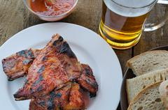 spareribs on grill with hot marinade, czech beer - stock photo