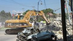 Vehicle drives around backhoe clearing debris (HD) Stock Footage