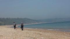 Old couple walk along a beach Stock Footage