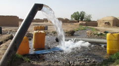 Water pours out of pipe from well pumped by diesel engine in afghanistan Stock Footage