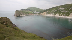 Lulworth Cove Dorset England UK with boat entering harbour Stock Footage
