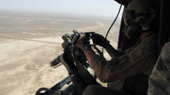 Helicopter door gunner readies machine gun and looks for target (HD) Stock Footage
