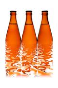 Three beer bottles in a row - stock photo