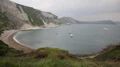 Boat entering Mupe Bay east of Lulworth Cove Dorset England Stock Footage