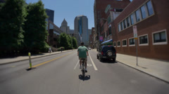 4K Man Rides in the Bike Lane in Pittsburgh Stock Footage