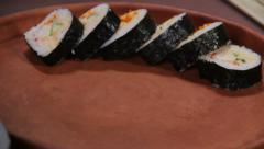 Close-up cook serving mouth-watering sushi rolls on wooden plate Stock Footage