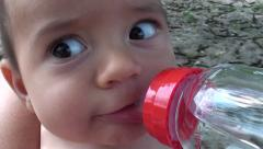 Baby drinking water from bottle close up Stock Footage