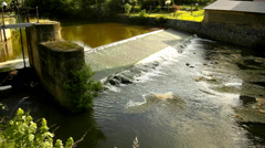 Old water of small river flow over small stony weir. Small water flowers Stock Footage
