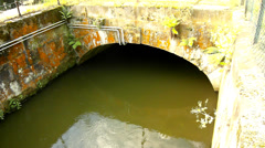 Water of small river flow into small stony tunnel or bridge. Green muddy water Stock Footage